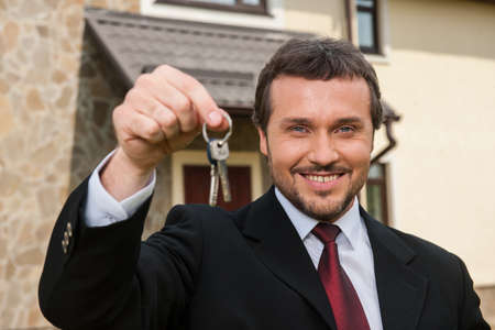 closeup on smiling real estate agent ready to sell house. Male real etate agent in front of home holding keys Stock fotó