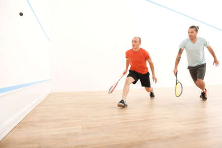 Two men playing match of squash. Squash players in action on squash court Foto de archivo