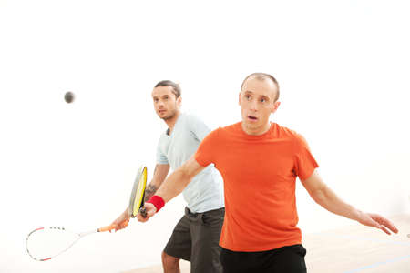 Two men playing match of squash. closeup view of squash player in action reaching on squash court