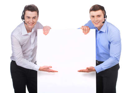 Smiling customer service male operator pointing to blank white billboard. two males standing next to white board and smiling