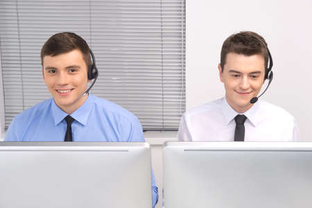 front view of customer service employee with headphones on white. two men working in call center and smiling