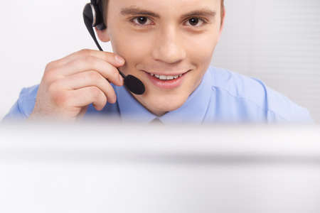 handsome technical support operator working on computer. male face with headset portrait at bright call center helpdesk support office