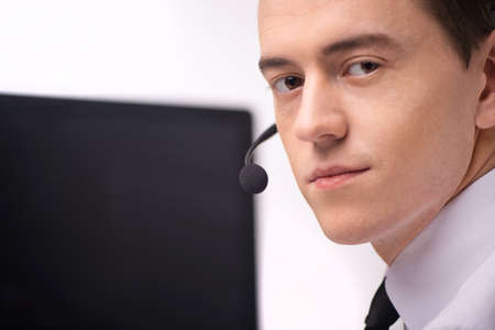computer operator: handsome technical support operator working on computer. businessman with headset portrait at bright call center looking into camera