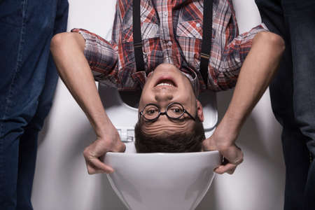 man is standing upside down on toilet bowl. closeup on two man holding man over toilet seat