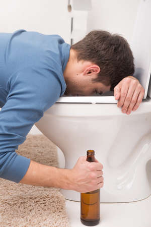 Drunk man sleeping on toilet and holding bottle. sick man is vomiting and feeling bad photo
