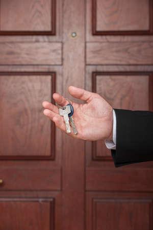 closeup on man hand holding keys to apartment door. real estate agent with keys on brown door Stock fotó