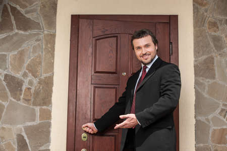 welcome door: realtor opening wooden door and smiling welcoming. brown wooden door and business man in suit and tie