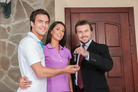 Salesman giving keys to property owners. businessman near entrance door with young couple outside photo
