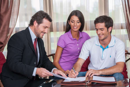 closeup on happy man signing agreement on new house. agent giving documents to young couple purchasing new house