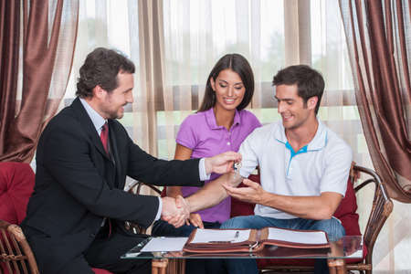 purchasers: closeup on happy man taking keys to new house. agent giving keys to young couple purchasing new house and shaking hands