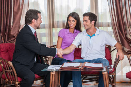closeup on two man handshaking to signed agreement. agent looking at young couple purchasing new house and shaking hands