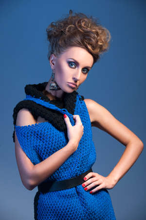 beautiful blonde woman wearing blue dress on blue background. knitted dress without sleeves on pretty girl
