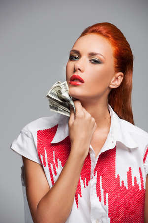 Young hot woman with dollars on grey background. closeup on pretty redhead girl holding money