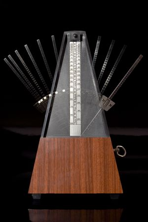Classic wooden metronome in motion on dark background photo