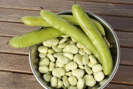 Bowl of broad beans and pods on garden table