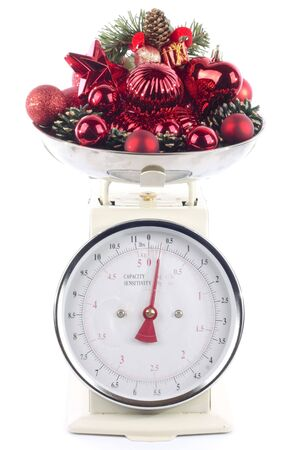 Weighing scales with christmas decorations isolated on white