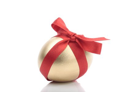 Gold egg with red ribbon over white background Stock Photo - 4805467