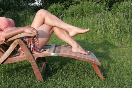 Woman relaxing on sunny  garden chair photo