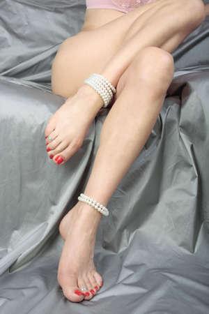 Beautiful woman  legs  over silver satin  fabric photo