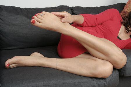 Beautiful woman  legs with  dress massaging aching feet photo