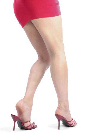 tacones rojos: las piernas de mujer sexy y talones rojos sobre blanco  Foto de archivo