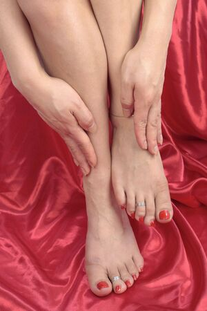 Woman feet and legs isolated over red background photo