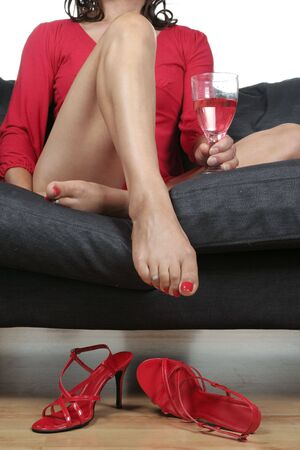 Beautiful woman  legs with wine drink relaxing on sofa