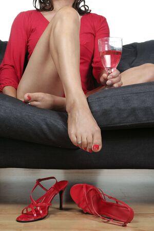 pies sexis: Piernas de la mujer hermosa con vino bebida relajante en sof�