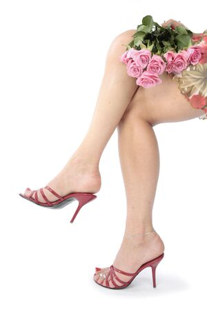 tacones rojos: Las piernas de la bella mujer y talones rojos con vestidos y flores sobre fondo blanco  Foto de archivo
