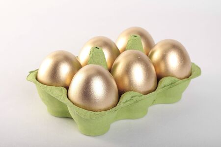 Golden Easter eggs in carton over white background photo