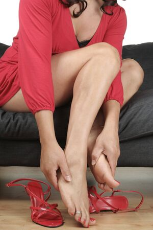 aching: Beautiful woman  legs with short red dress relaxing Stock Photo