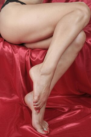 Woman feet and legs over red satin fabric photo