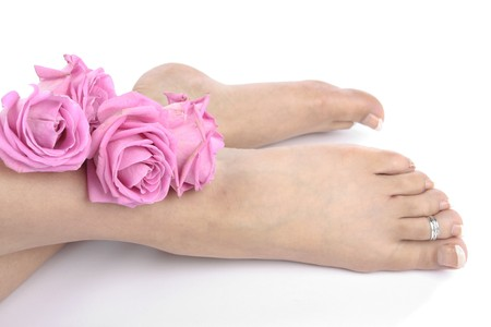 Woman  feet and flowers isolated over white background