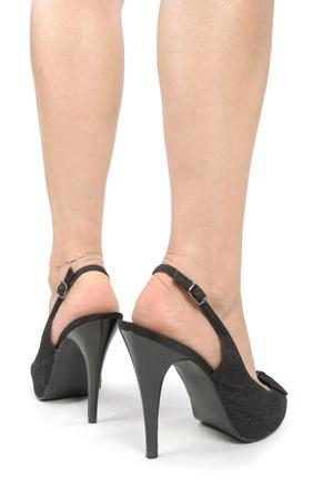 Piernas de la mujer con zapatos de tac?n negro sobre blanco