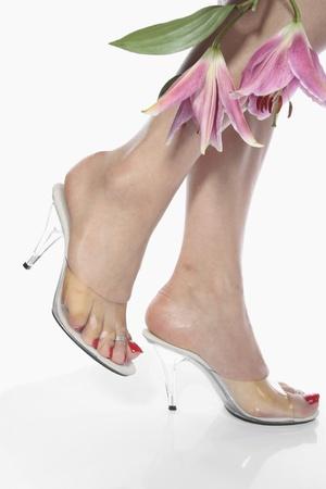 sensuel: Belle femme pieds et talon chaussures sur blanc Banque d'images