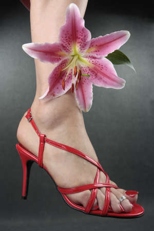 Beautiful woman feet putting on red shoes flower photo