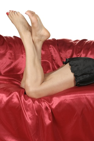 Woman legs with black nightie  isolated over red background photo