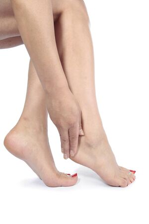 Woman massaging aching feet   over white photo