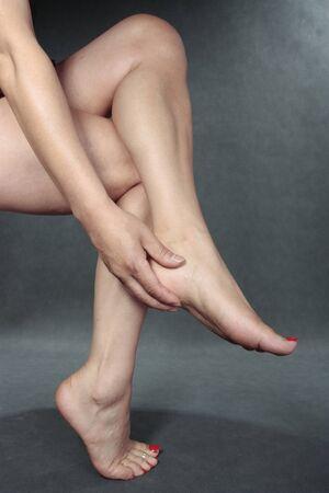 aching: Woman massaging aching feet Stock Photo