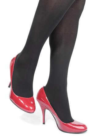 tacones rojos: Mallas de piernas de hermosa mujer con tacones rojos sobre blanco