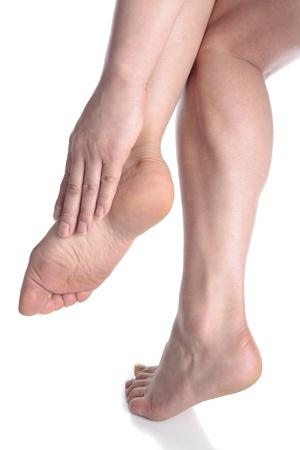 Woman massaging aching feet   over white