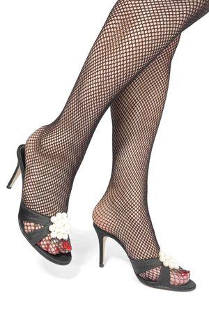 tacones negros: Mallas de piernas de hermosa mujer con tacones negros sobre blanco Foto de archivo