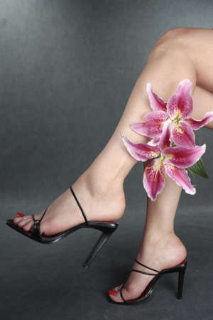 Beautiful woman legs black shoes and flowers Stock Photo - 9147132