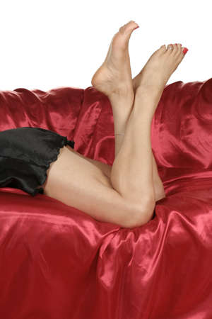nightie: Woman legs with black nightie  isolated over red