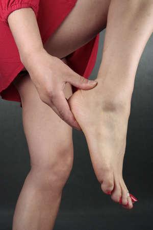 waxed legs: Woman feet red dress over grey