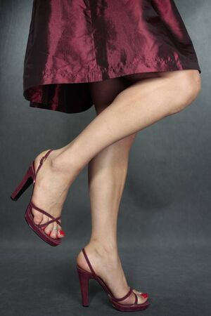 Beautiful woman dress legs red shoes  on grey photo