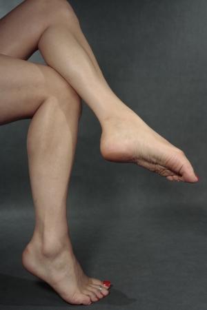 waxed legs: Woman feet  over grey
