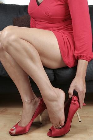 Woman legs putting on black heel shoes photo
