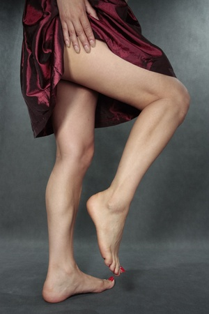 Beautiful woman  legs with red dress over grey photo