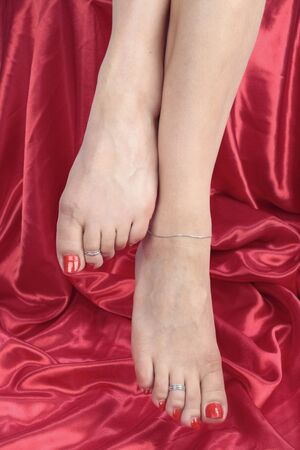 female feet: Woman  feet over red background